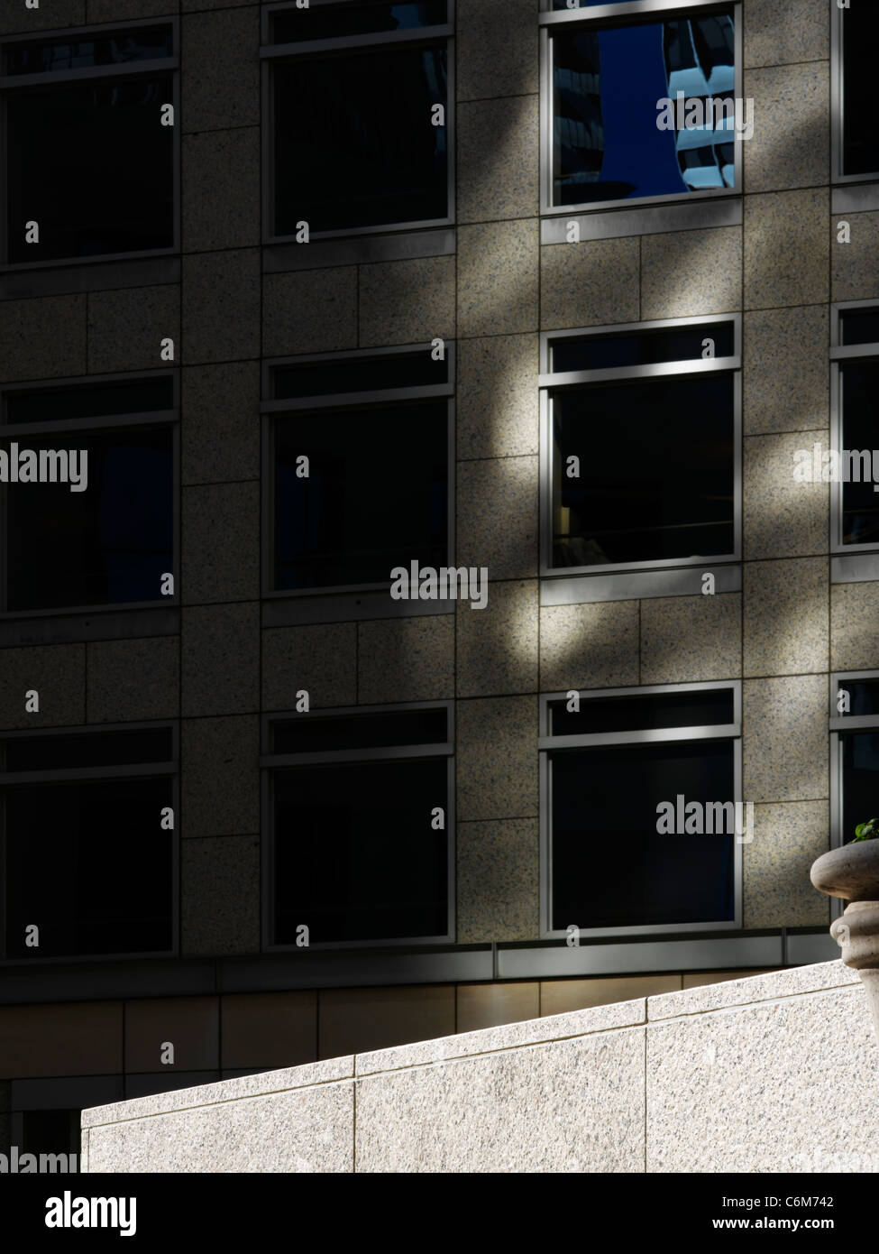 detail of empty office building plaza with stone ledge in bright sunshine seen dramatically against dark building - Stock Image