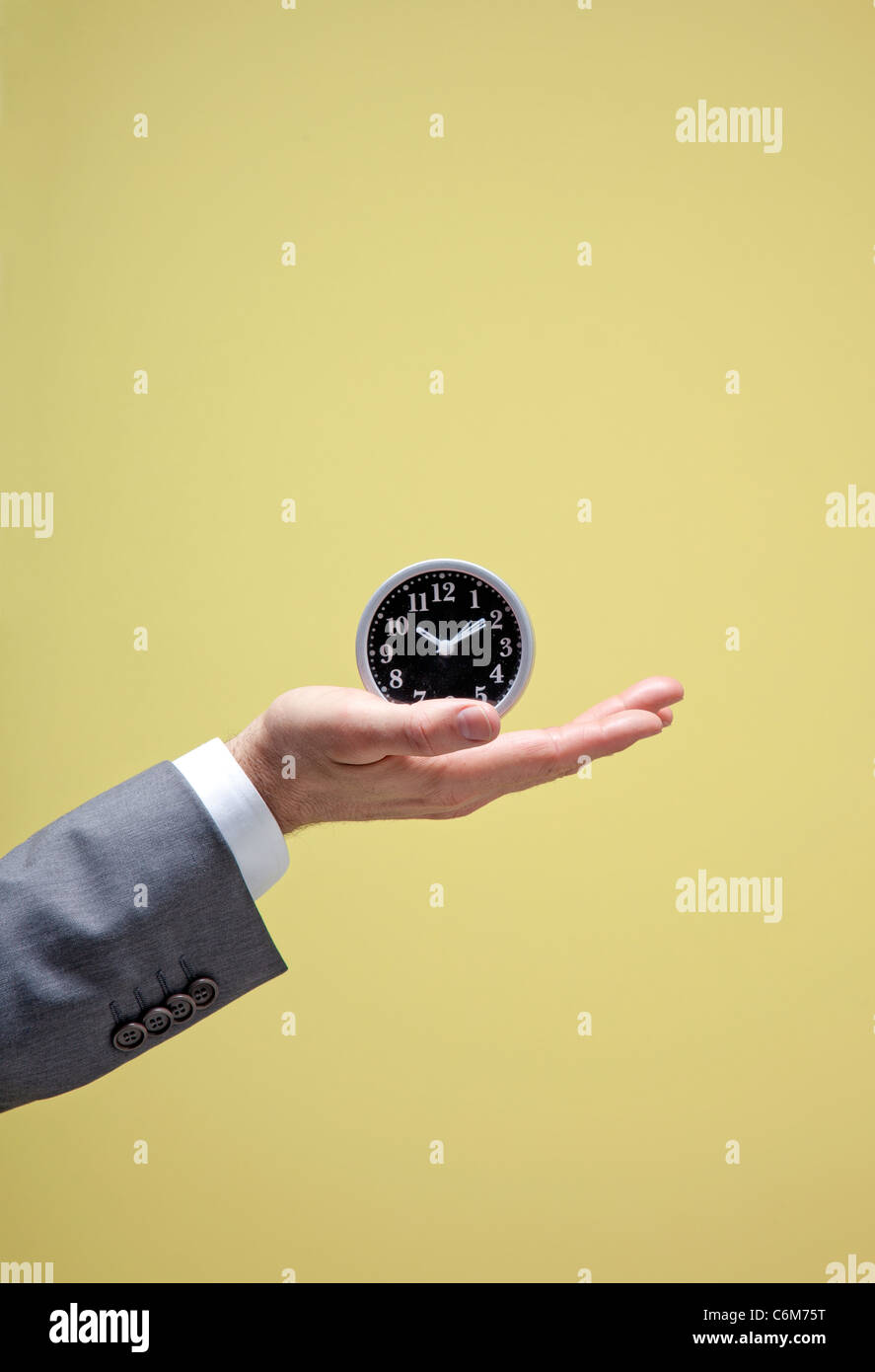 business man holds small clock in hand - Stock Image