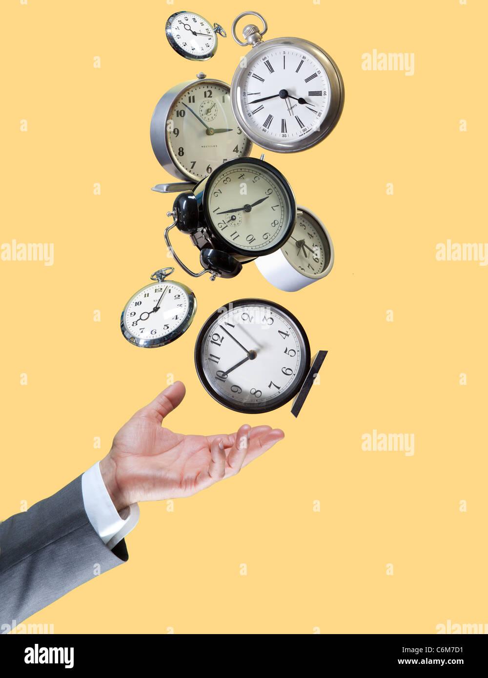 hand balances many clocks - Stock Image