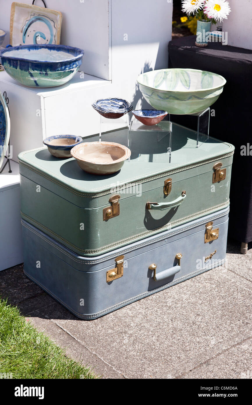 two immaculate vintage suitcases used as platform to display hand crafted ceramics at Edmonds farmers market Washington - Stock Image