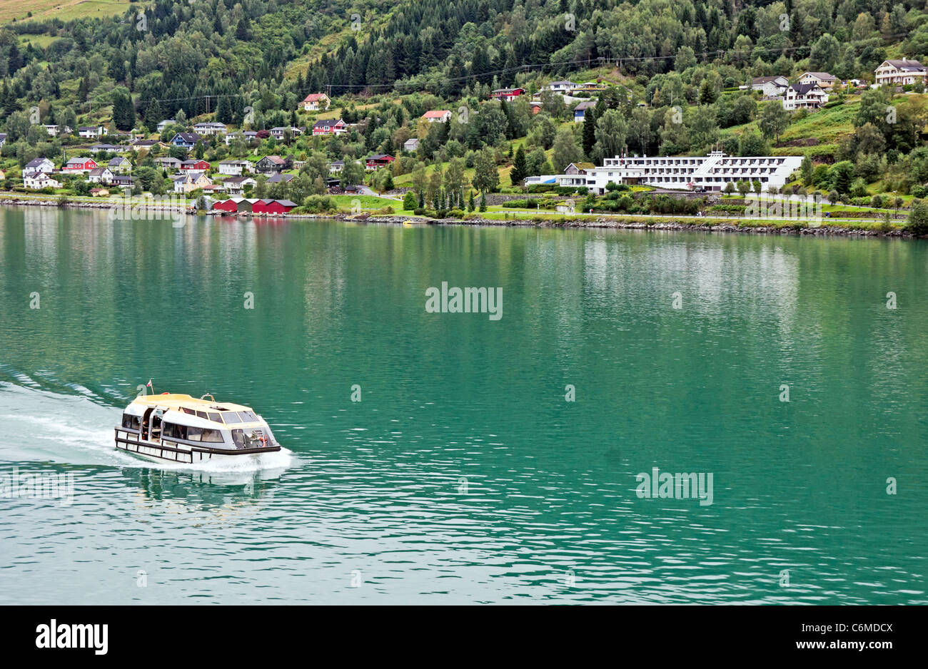 A tender is carrying passengers from a cruise liner to Olden pier on the Innvikfjorden in Norway with Olden Fjordhotel - Stock Image