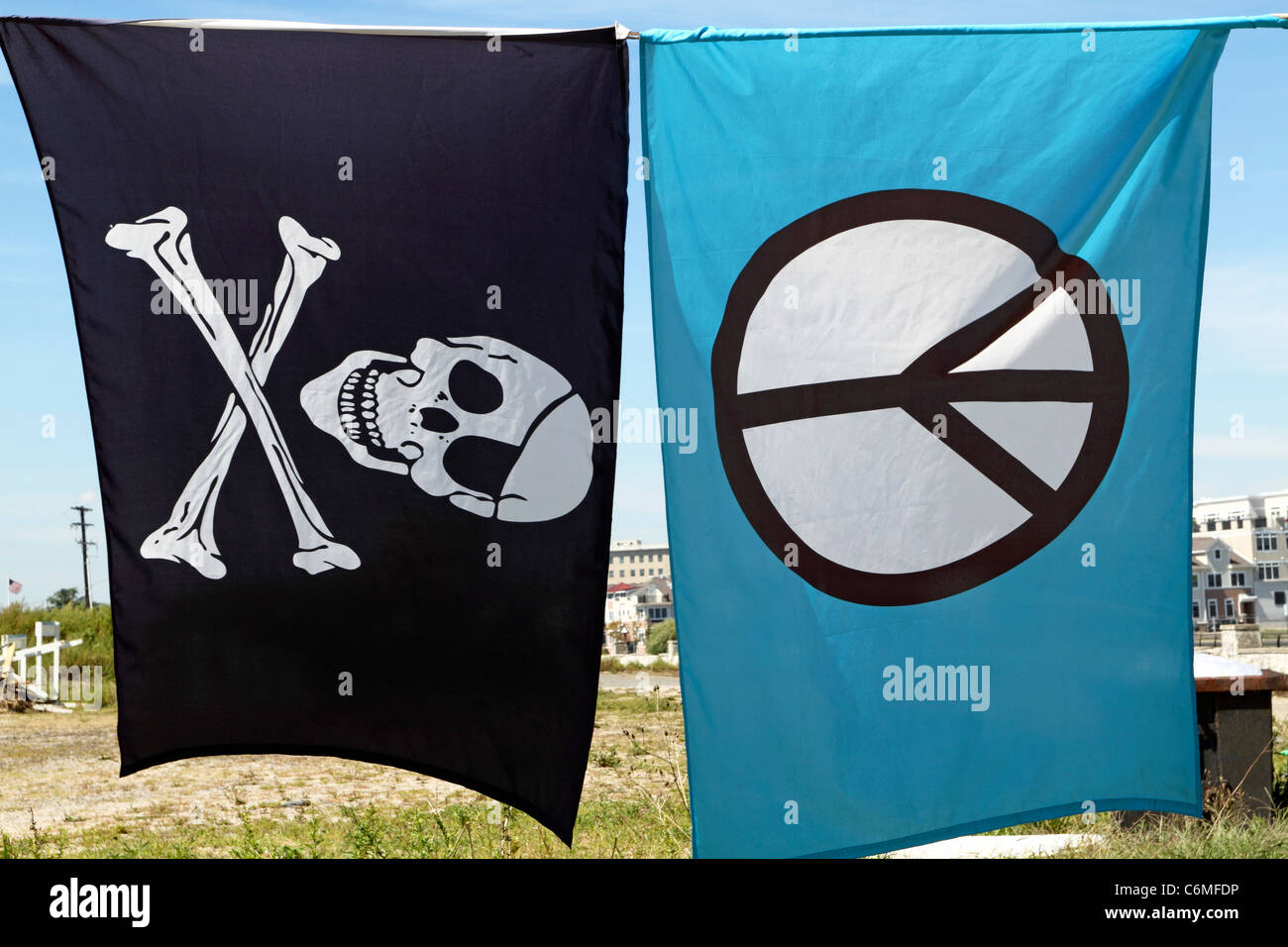 A Jolly Roger pirate banner and a Peace Sign banner flying next to each other amid a row of banners Stock Photo