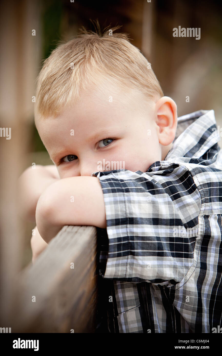 Young boy sneaking a glance leaning on a fence - Stock Image