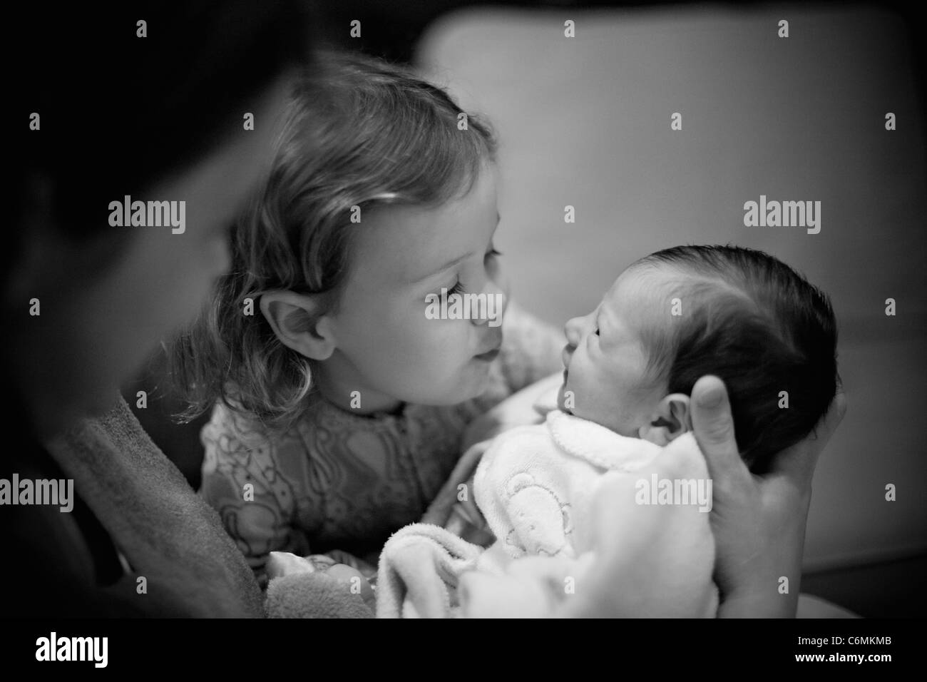 Young girl and her newborn baby sister - Stock Image