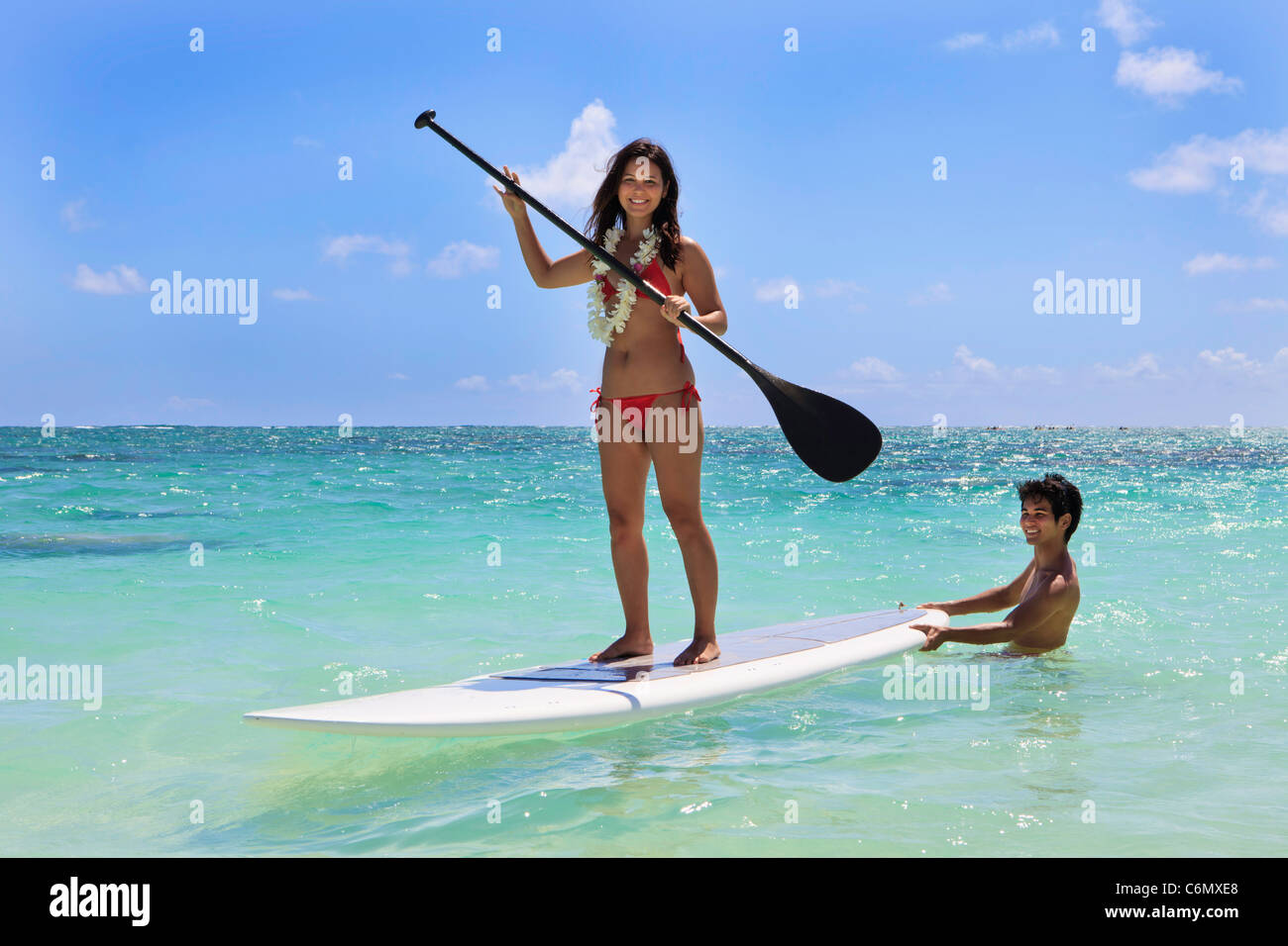 young couple with their paddle board in hawaii - Stock Image