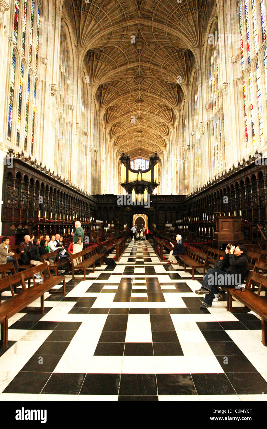 A view of the black and white tiled floor, pews and fan vaulted ceiling at King's College, Cambridge University Stock Photo