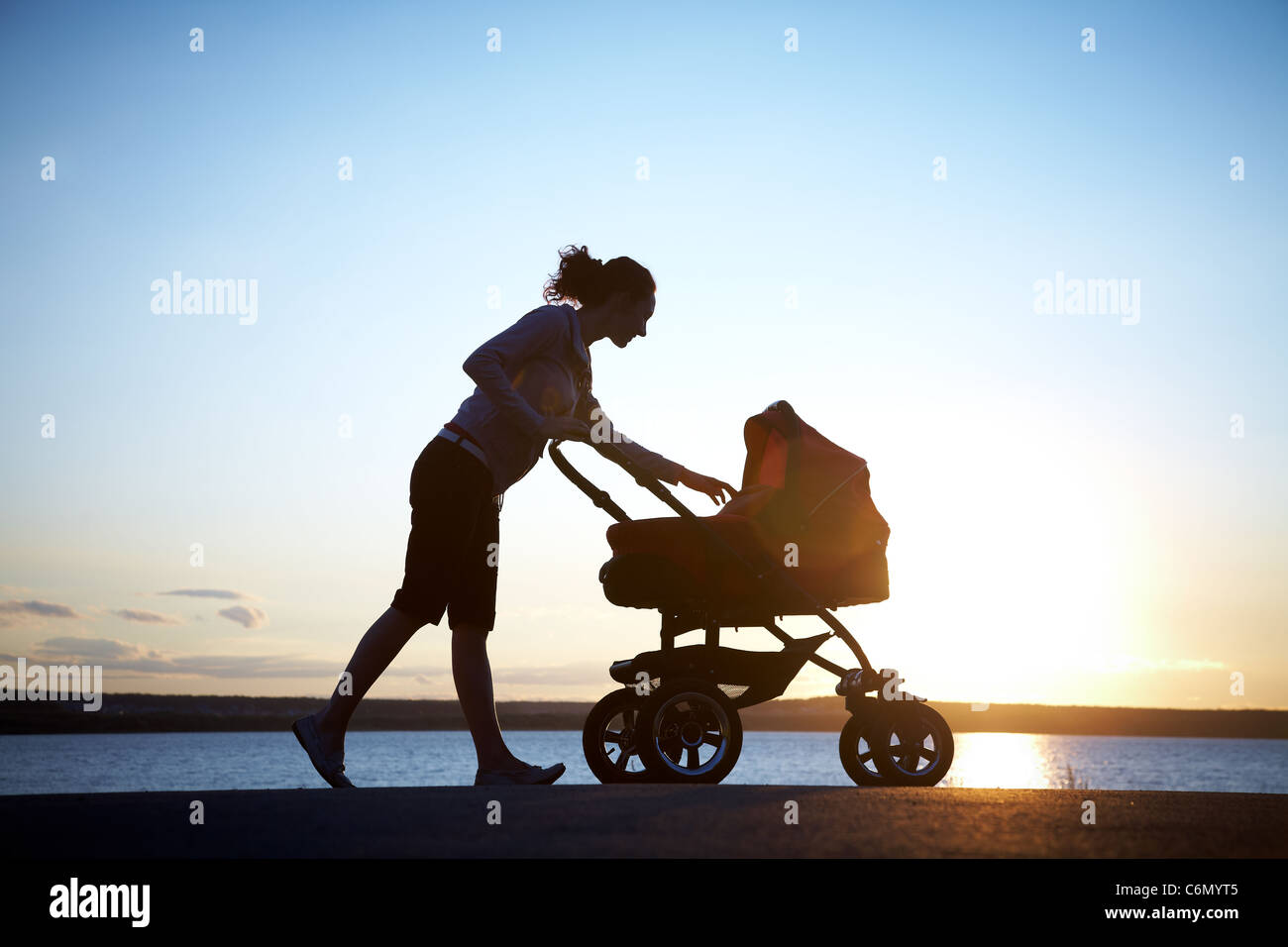 Silhouette of young mother enjoying motherhood - Stock Image