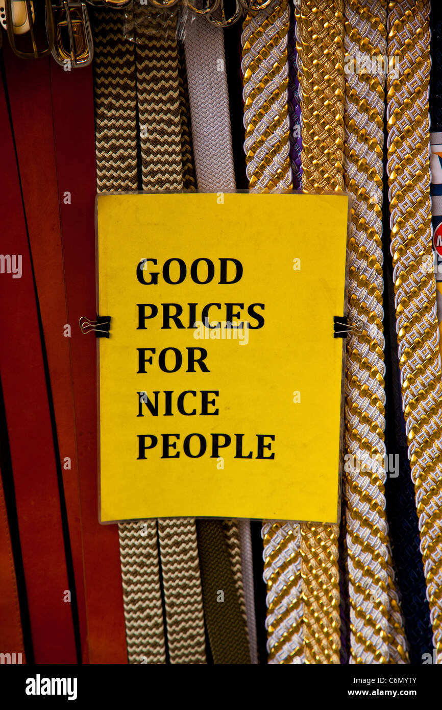 Belts displayed at the leather market in Florence Italy with a sign saying 'Good prices for nice people'. - Stock Image