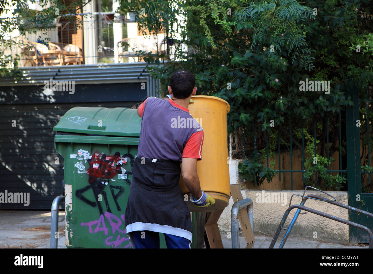 Road sweeper in Athens emptying a mobile bin into the roadside refuse bins - Stock Image