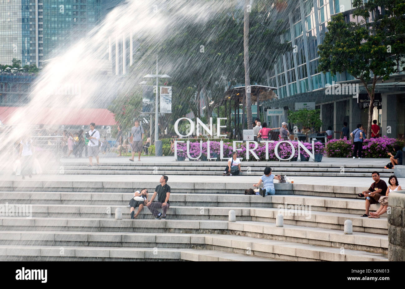 Tourists at One Fullerton by the Merlion fountain statue, Singapore Asia - Stock Image