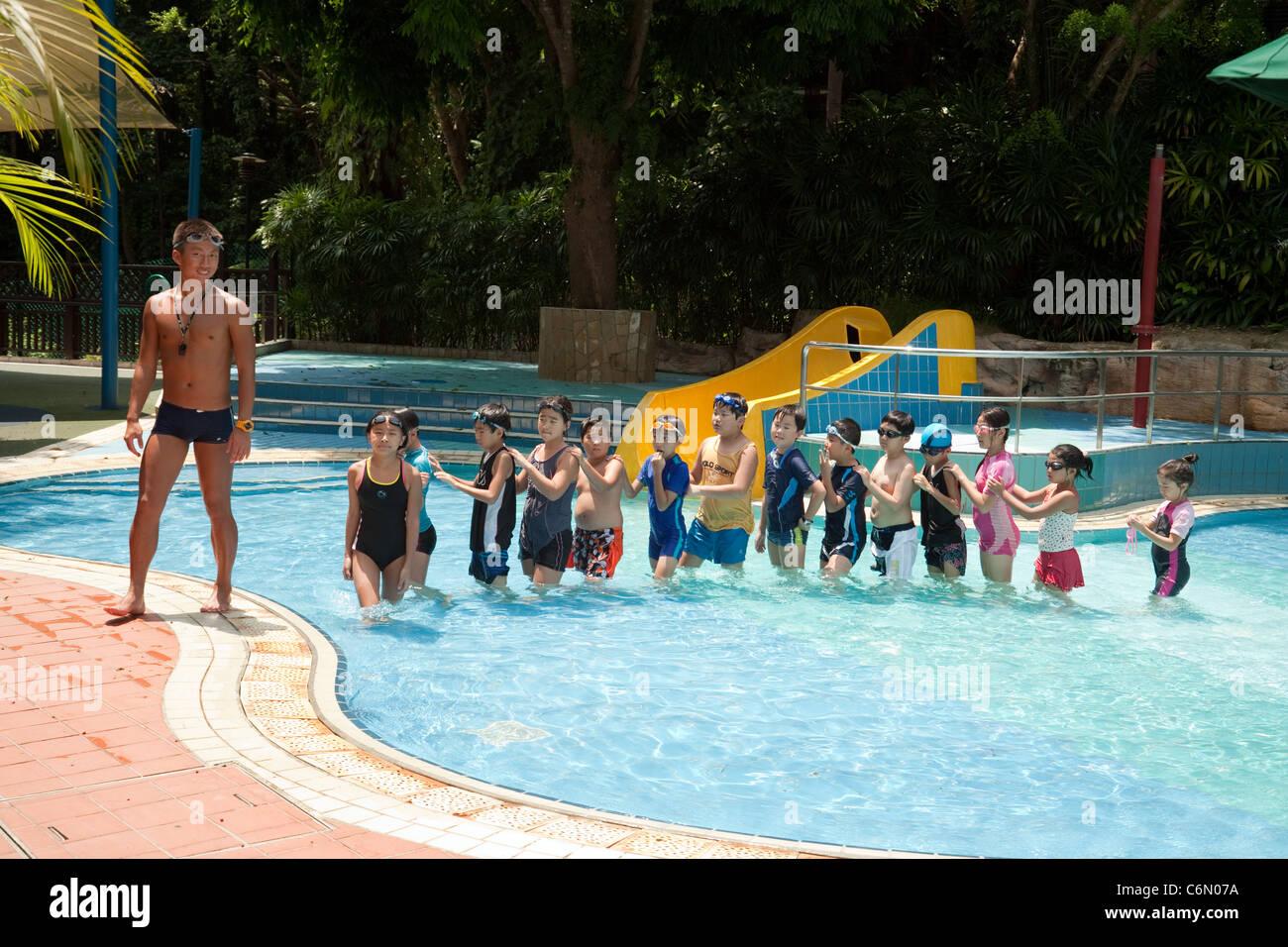 Primary schoolchildren having a swimming lesson with their teacher, Singapore, Asia Stock Photo