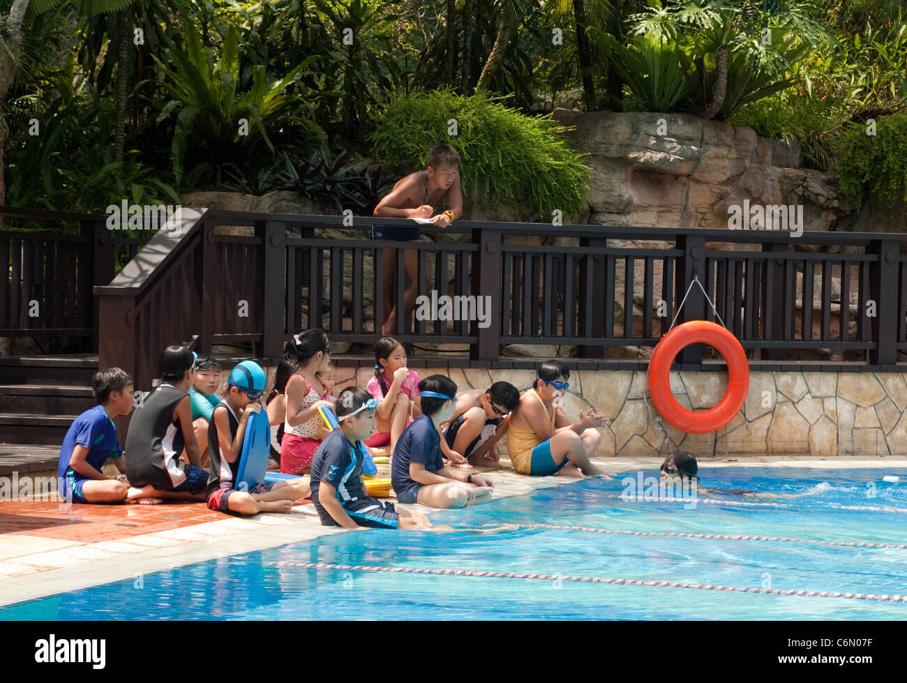 Primary schoolchildren having a swimming lesson with their teacher, Singapore, Asia - Stock Image
