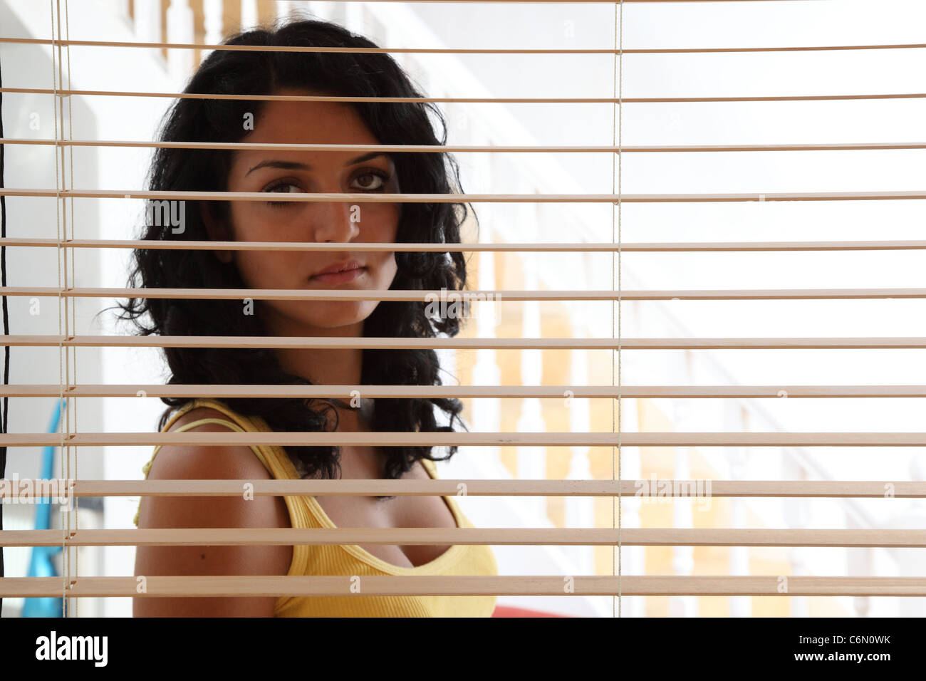 Woman behind a wooden blind looking out. Stock Photo