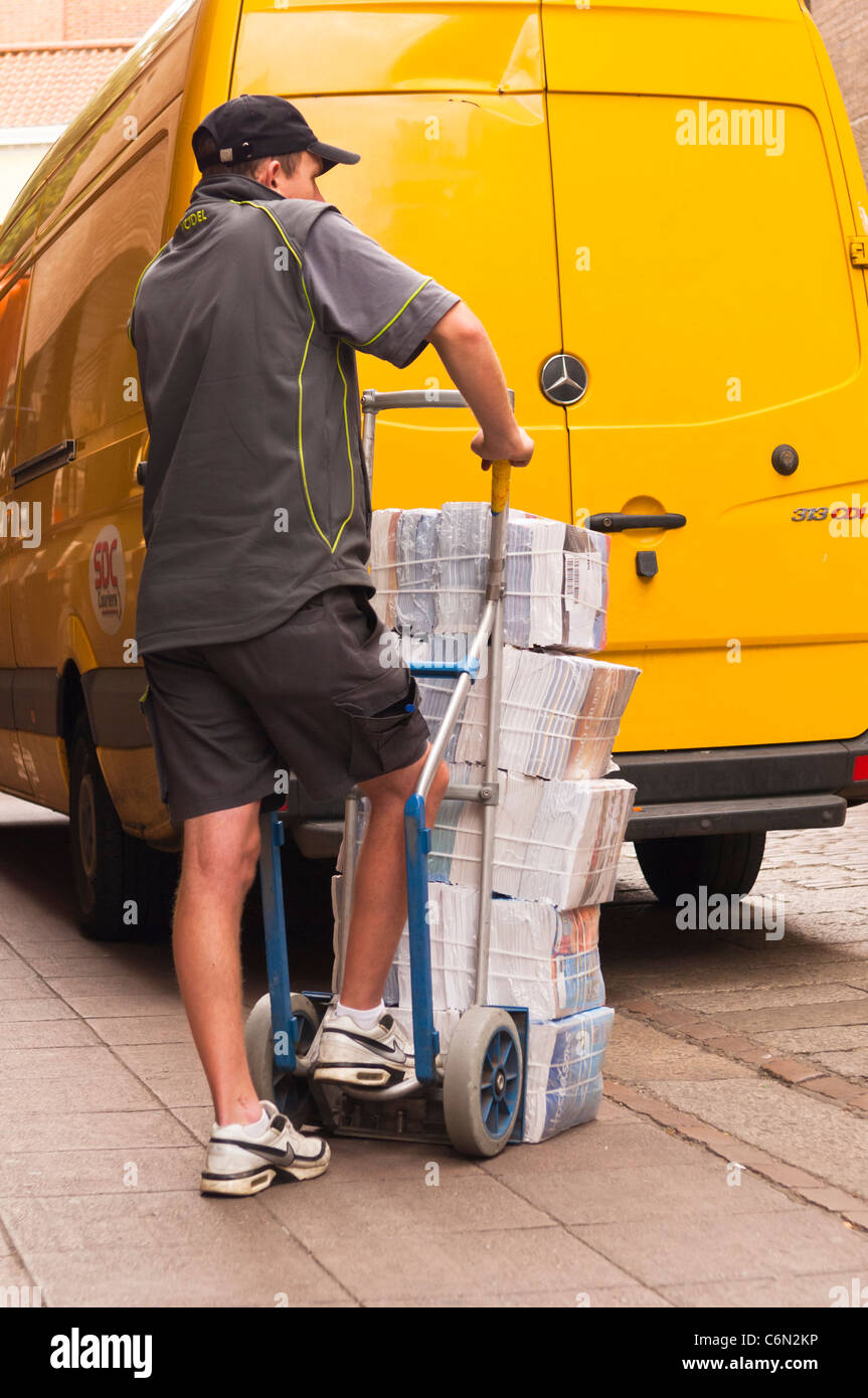 A courier from SDC couriers delivering goods on a sack barrow in Norwich , Norfolk , England , Britain , Uk - Stock Image