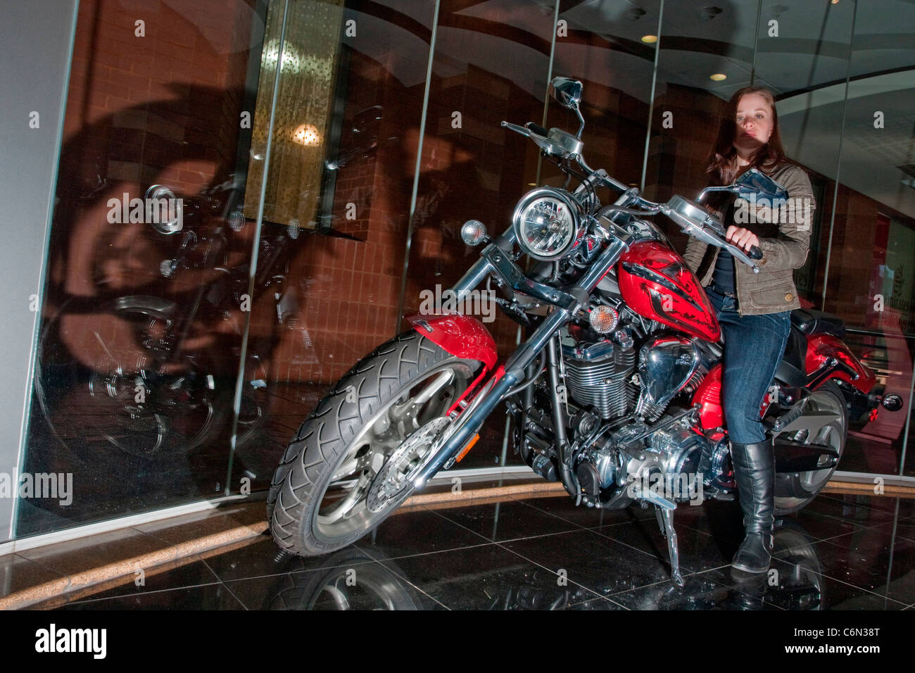 Young girl posing on Yamaha bike in showroom - Stock Image