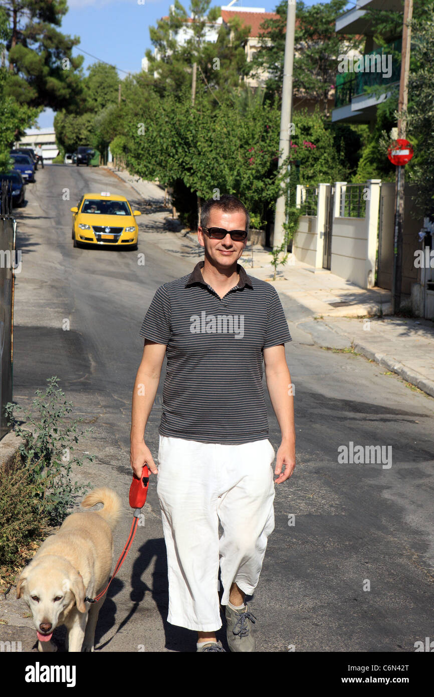 Man walking his dog in Athens suburbs - Stock Image
