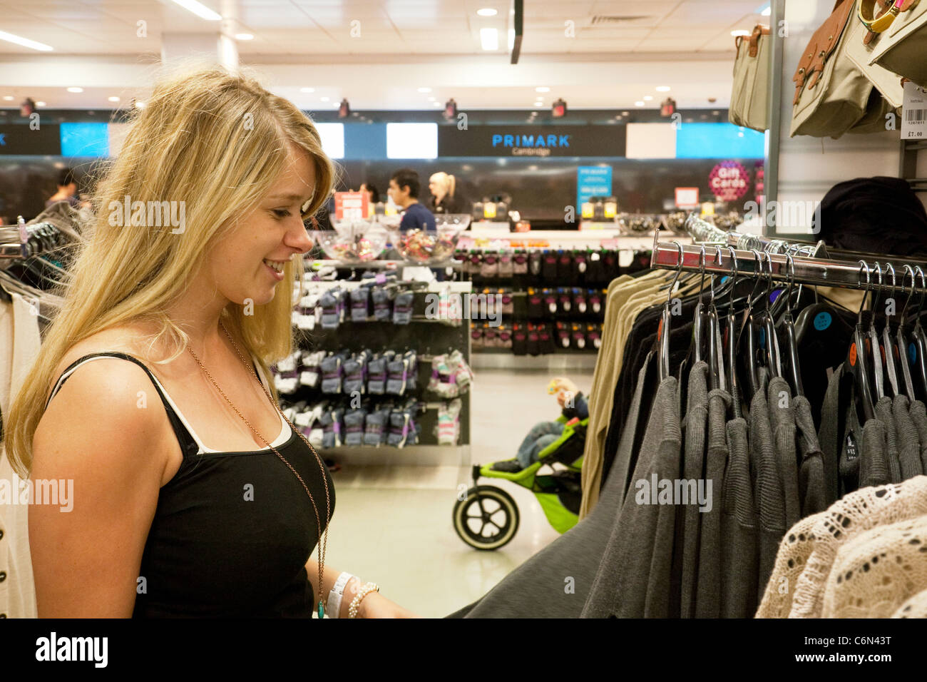 A teenage girl shopping inside Primark clothes store Cambridge UK - Stock Image