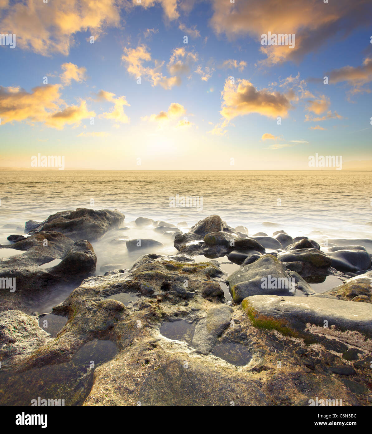 Beautiful sundown at rocky beach. Water in motion blur. - Stock Image