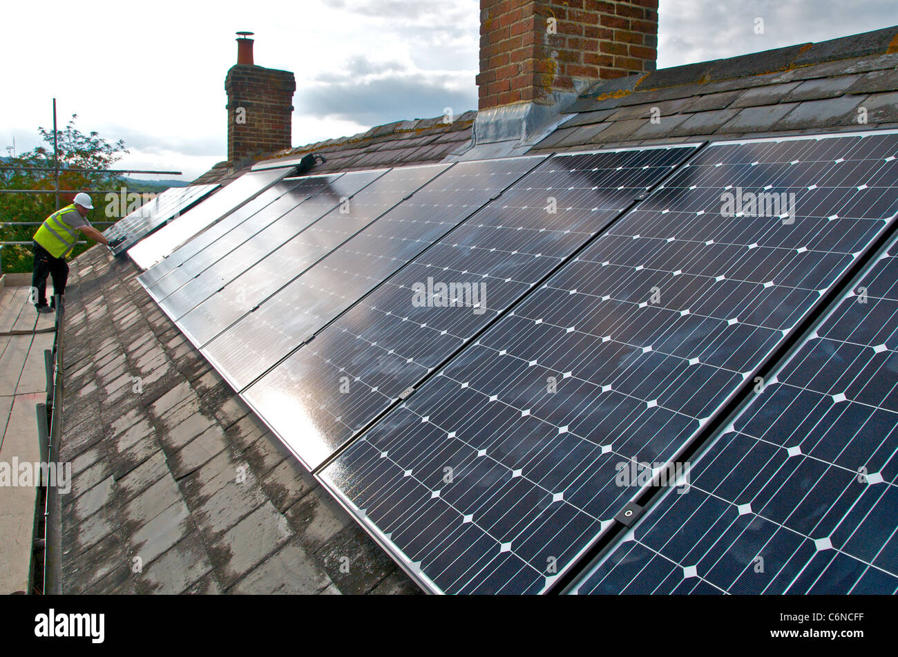 Photovoltaic panels on a roof using solar energy to create electricity - Stock Image