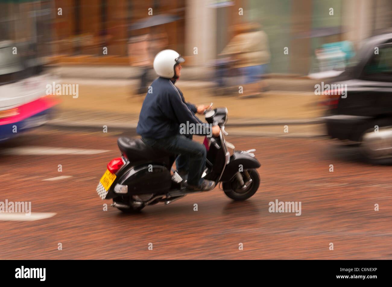 A man on a scooter drives through the city showing deliberate motion blur in Norwich , Norfolk , England , Britain - Stock Image