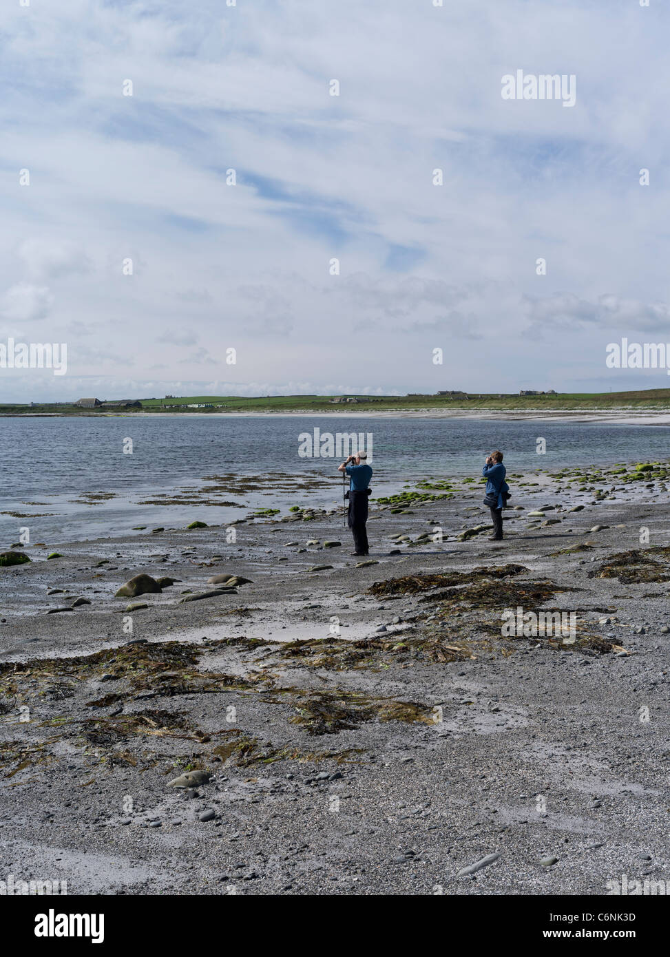 dh  PAPA WESTRAY ORKNEY Two birdwatchers watching with binoculars seashore beach bird watchers - Stock Image