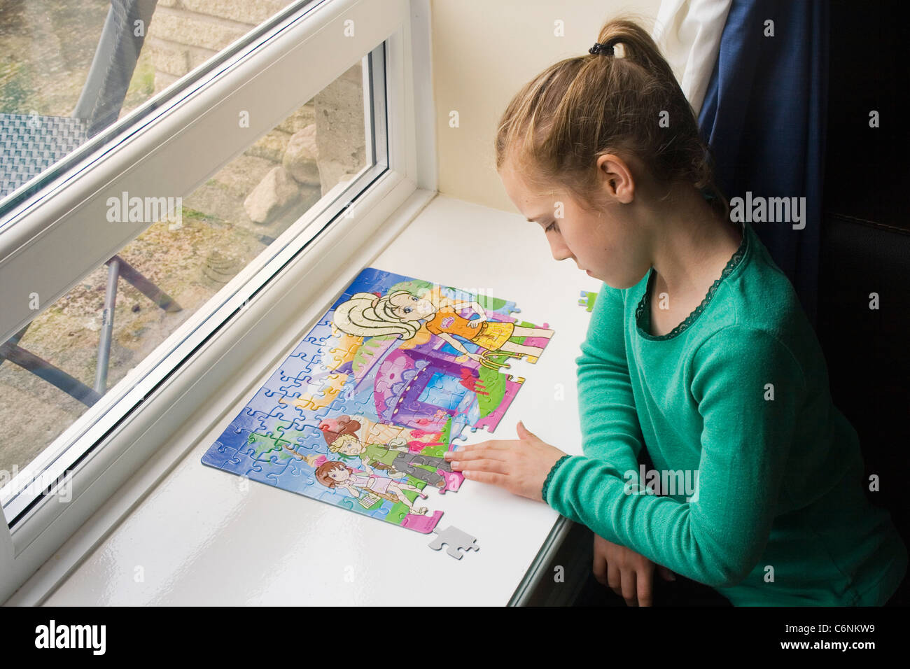 Eleven year old girl doing a jigsaw puzzle. - Stock Image