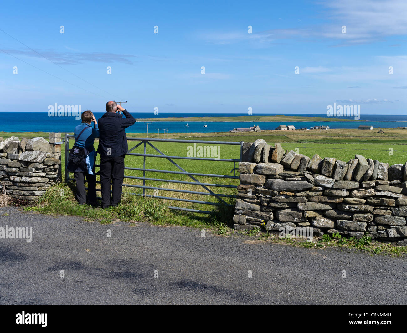 dh  PAPA WESTRAY ORKNEY Two birdwatchers viewing grass fields with binoculars people birds watchers - Stock Image