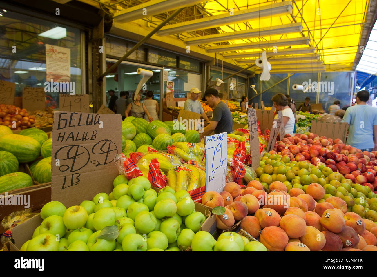 Clients peruse the stalls of a fruit and vegetables vendor on 86th Street in the New York City borough of Brooklyn - Stock Image