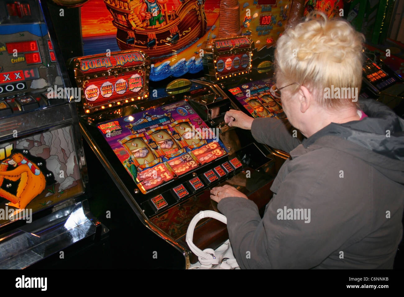 Woman playing slot machine. - Stock Image