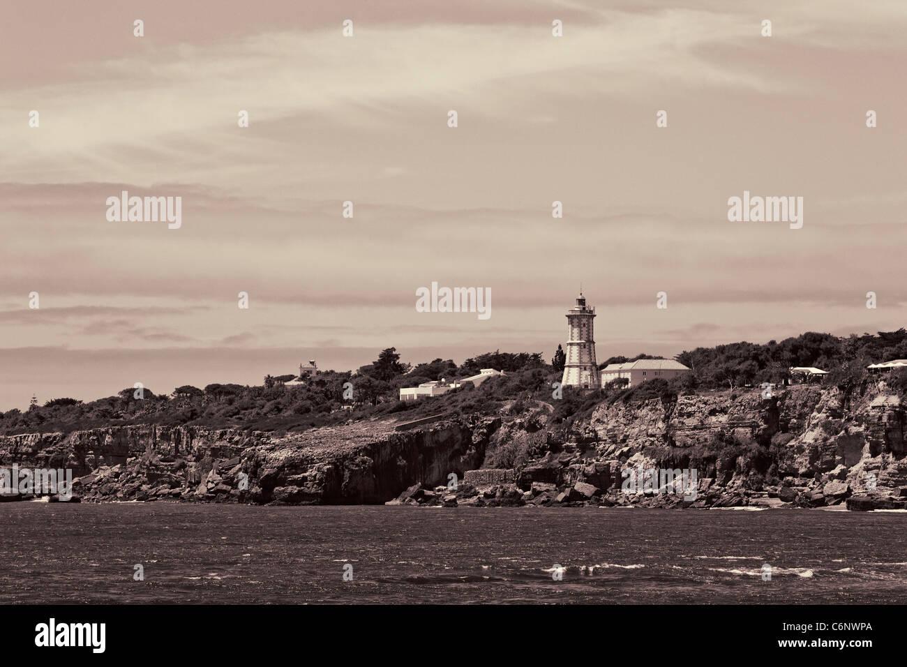 Light tower at shore near charm Boca do Inferno located close to the Portuguese city of Cascais. Stock Photo