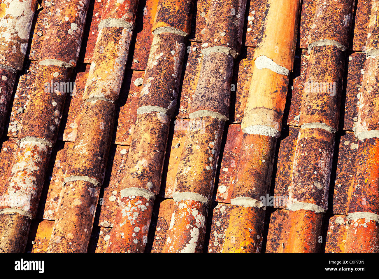 Close up of old, cylindrical red clay roof tiles on property. Stock Photo