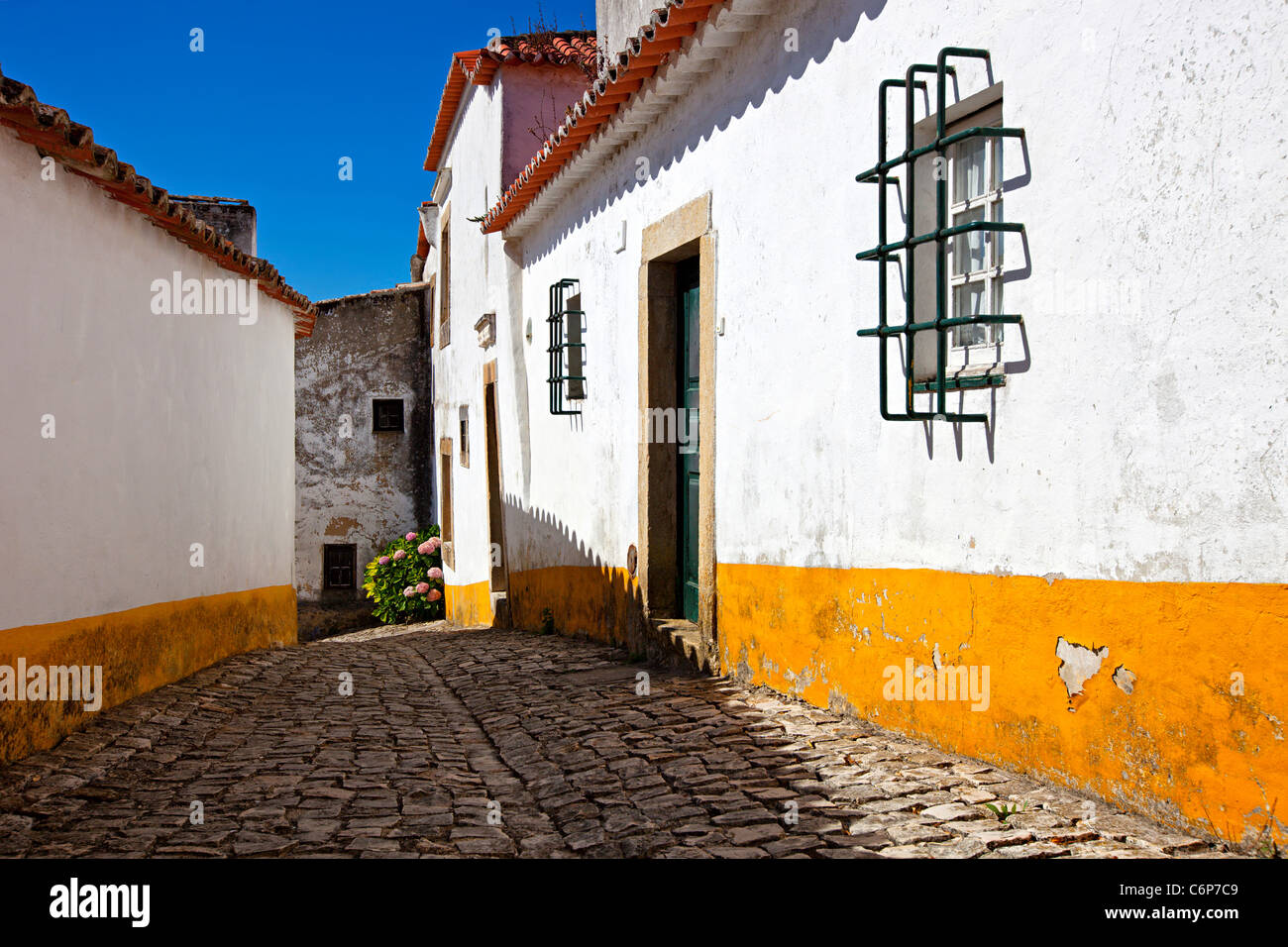 Narrow cobbled street in old medieval Obidos village, Portugal. Houses with white walls and yellow strips. Stock Photo