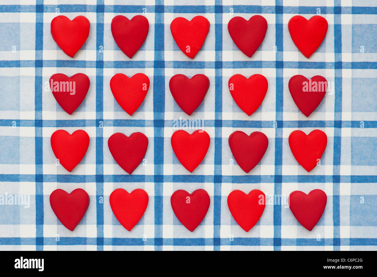 Red coloured love hearts on a blue chequered background - Stock Image