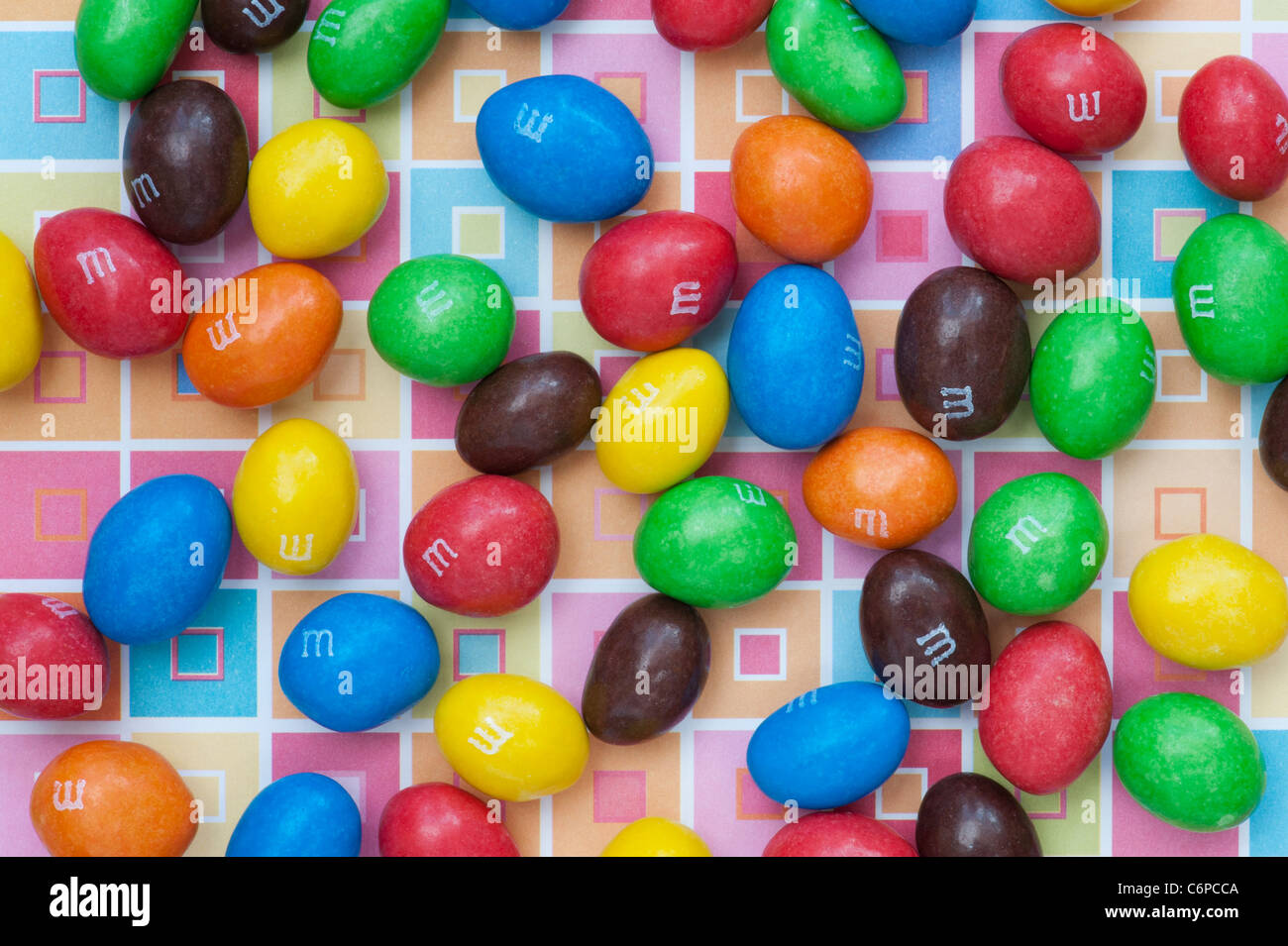 M & M s on colourful square patterned background - Stock Image