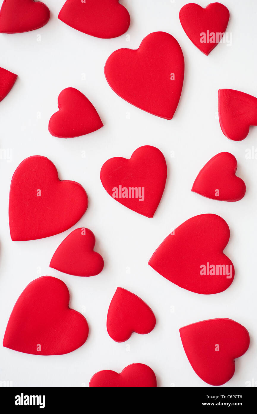 Red coloured love hearts on white background - Stock Image