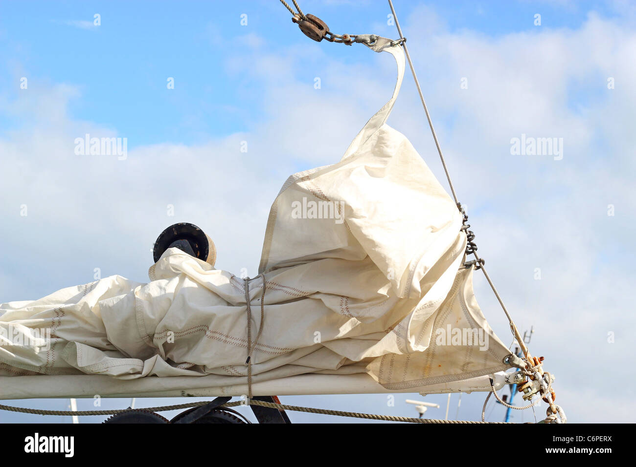 White sail being furled on a sailboat at dock in the harbor with bright blue sky and clouds in the background. - Stock Image