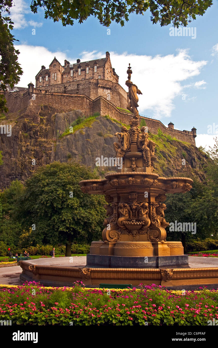 Edinburgh Castle on volcanic castle rock from West Princes Street Gardens with Ross Fountain sculpture by Jean-Baptiste - Stock Image