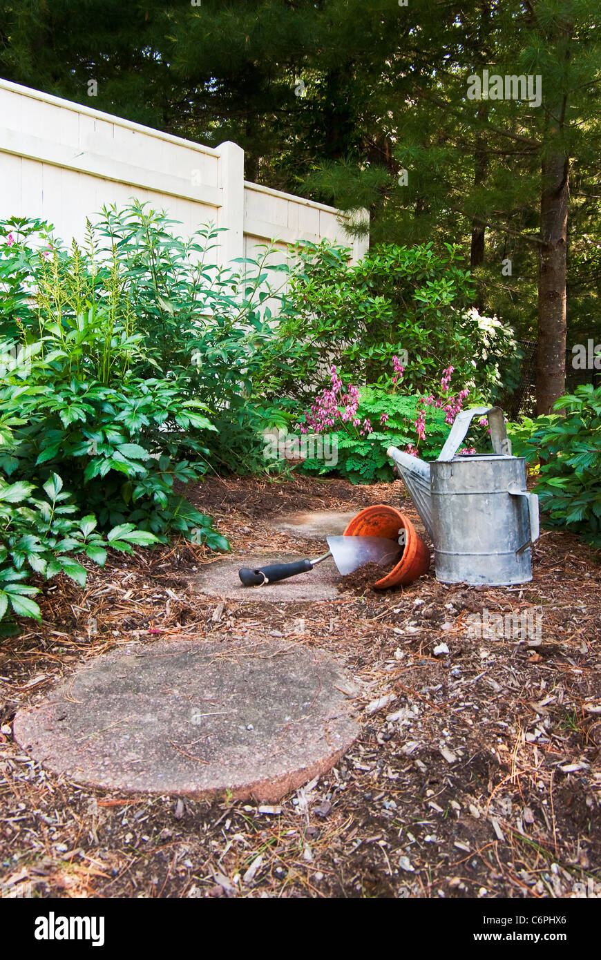 An old watering can sits next to a trowel and clay pot that are ready for flowers Stock Photo