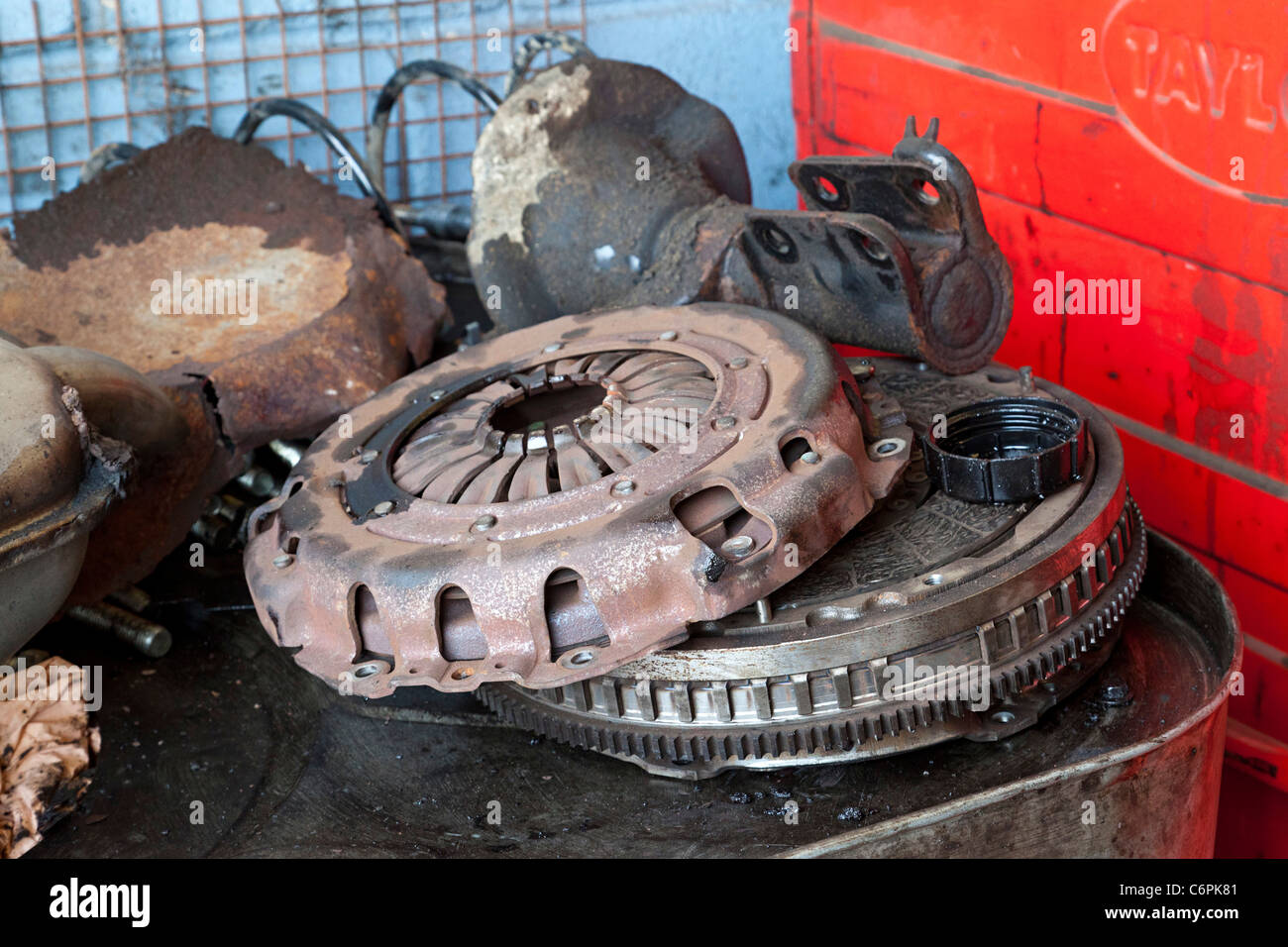old car clutch parts disassembled in a garage workshop in uk - Stock Image