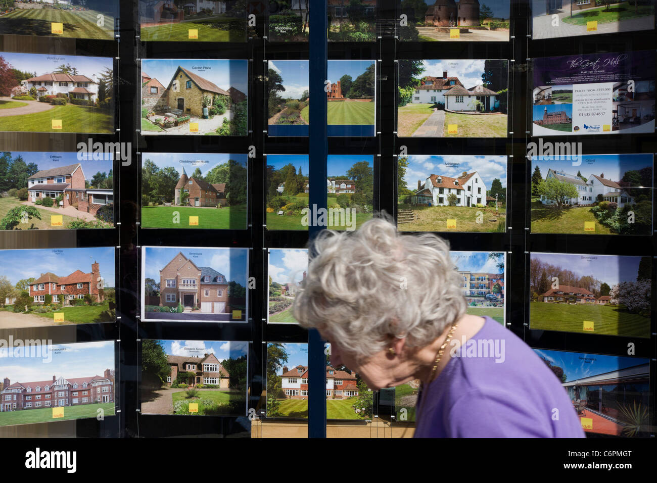 Elderly lady walks past an assortment of properties are displayed in a Sevenoaks estate agent's high street - Stock Image