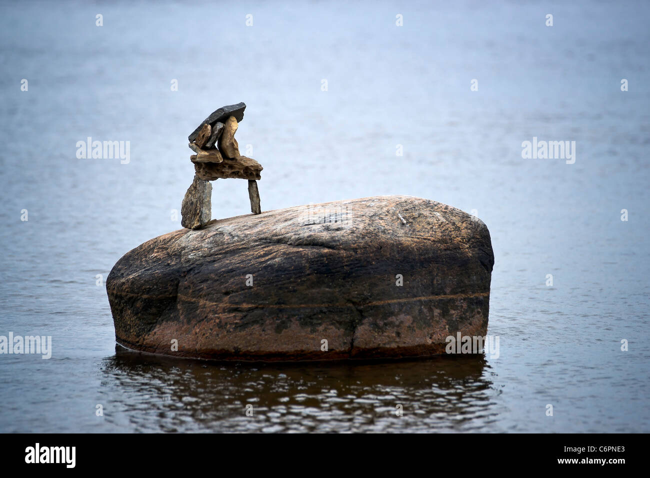 A small inuksuk (inuckshuk) sits on top of a lone boulder in surrounding water. - Stock Image