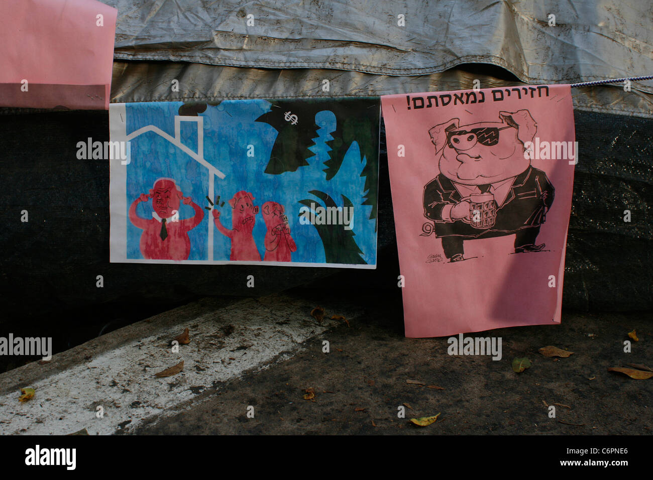 Cynical posters against the social inequality in Israel hanged up from activists in a tent city in Tel Aviv, Israel. - Stock Image