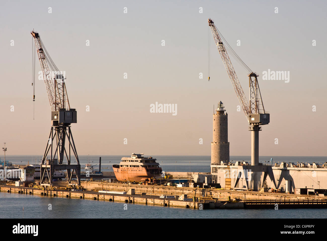Cranes in a dry dock lit by early morning light - Stock Image