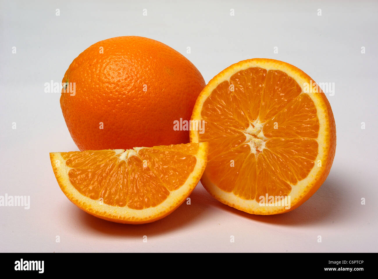 Orange and slices of oranges sit on a white background. - Stock Image