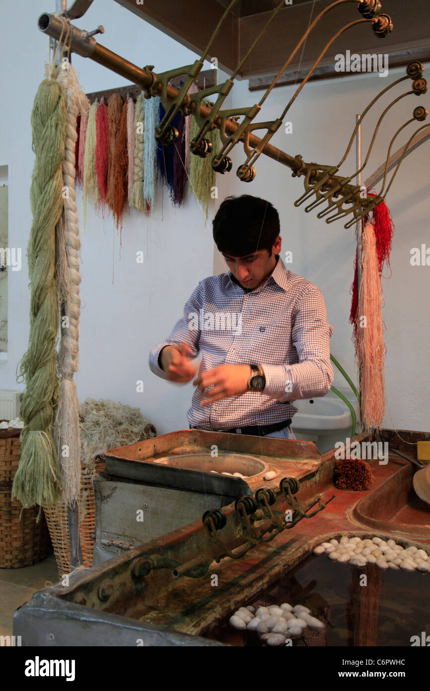 A youn man weaves silk on a hand loom at cappadocia. - Stock Image