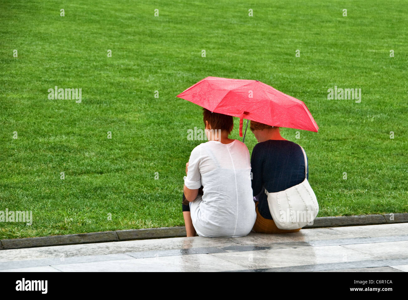 Two women sheltering under a red umbrella from the rain. View from the rear behind. Close up - Stock Image