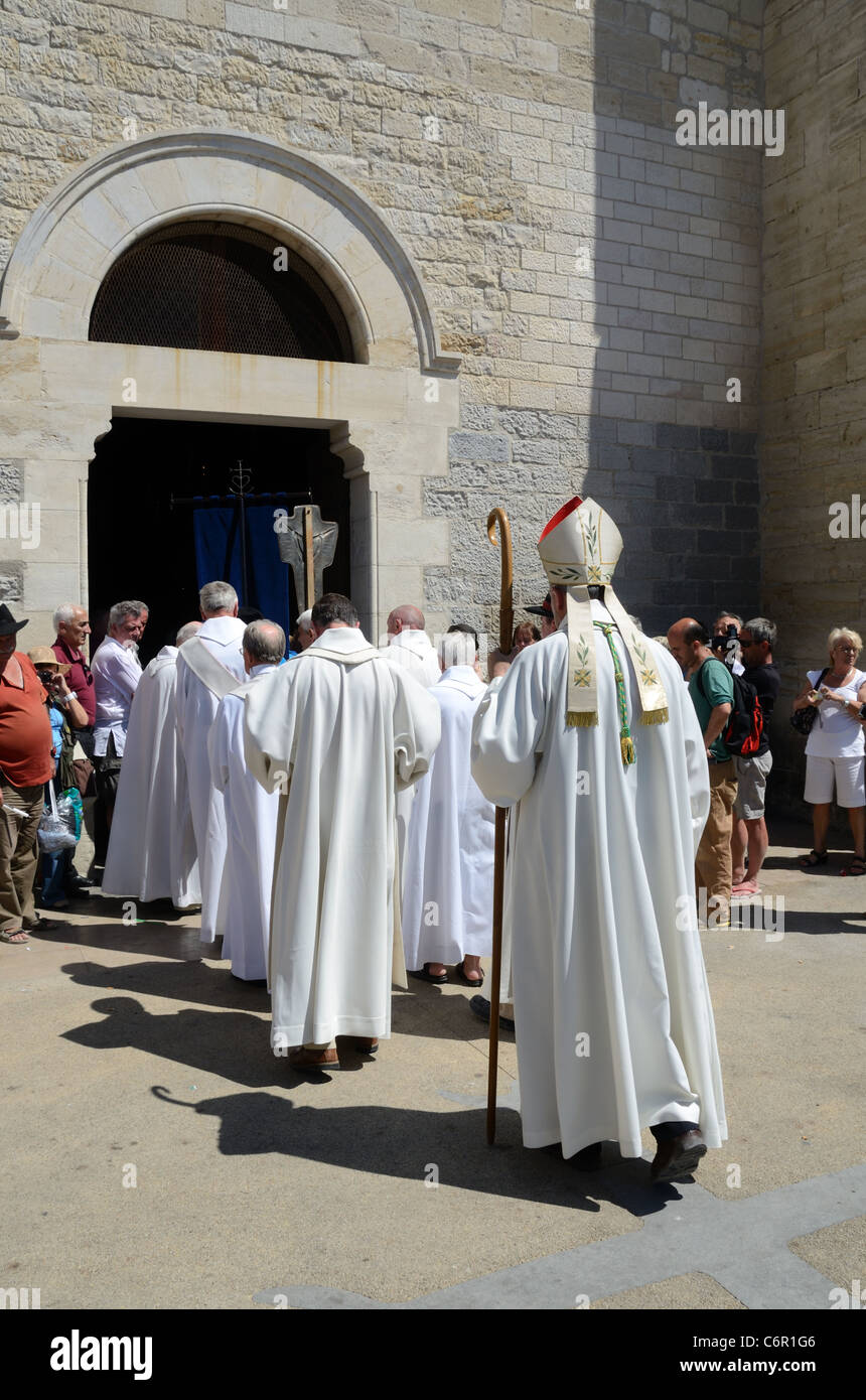Clergy wearing Cassocks Entering the Fortified Church of Les Saintes-Maries-de-la-Mer During a Gypsy Festival Camargue - Stock Image