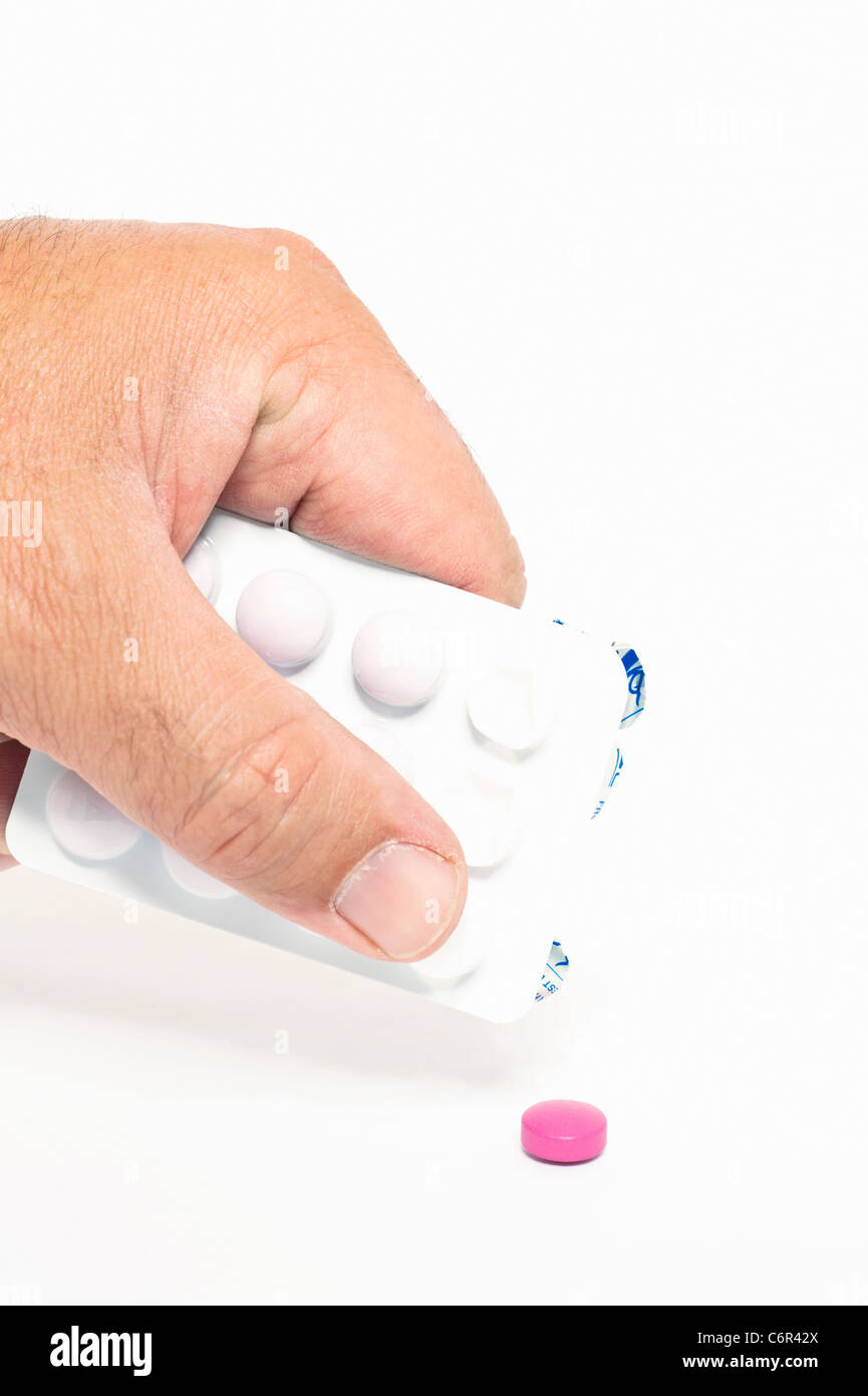 A person pushing a pink pill out of a blister pack - Stock Image