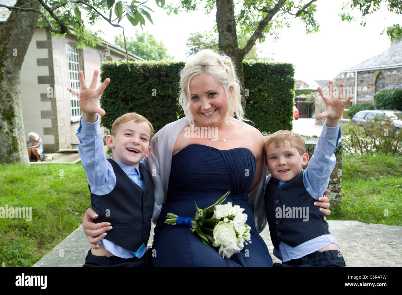 Matron of honour. A young mother with her 6 year old twins at a family wedding. - Stock Image