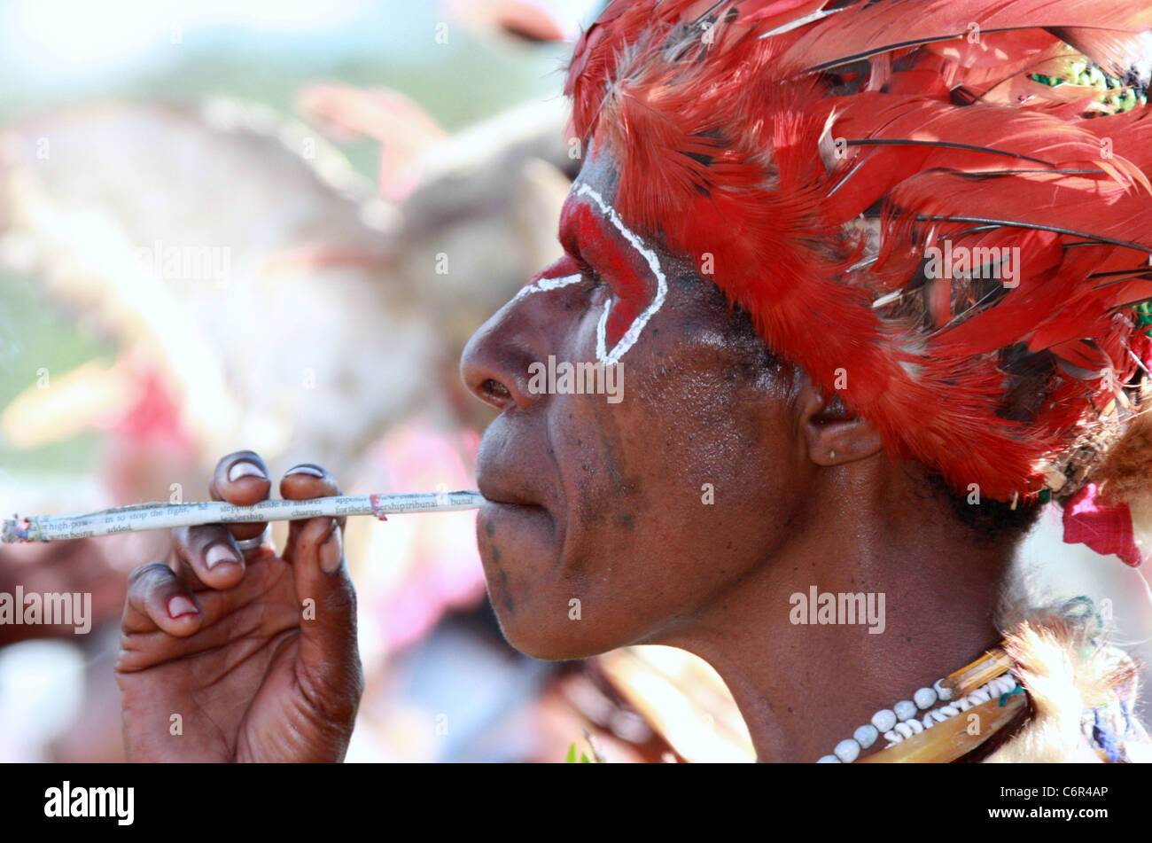 Tribeswoman from Papua New Guinea smoking a cigarette rolled from newspaper - Stock Image